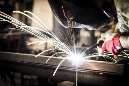 Worker welding steel in company.