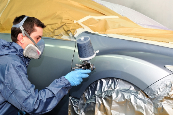 Worker painting a silver car in a paint booth.
